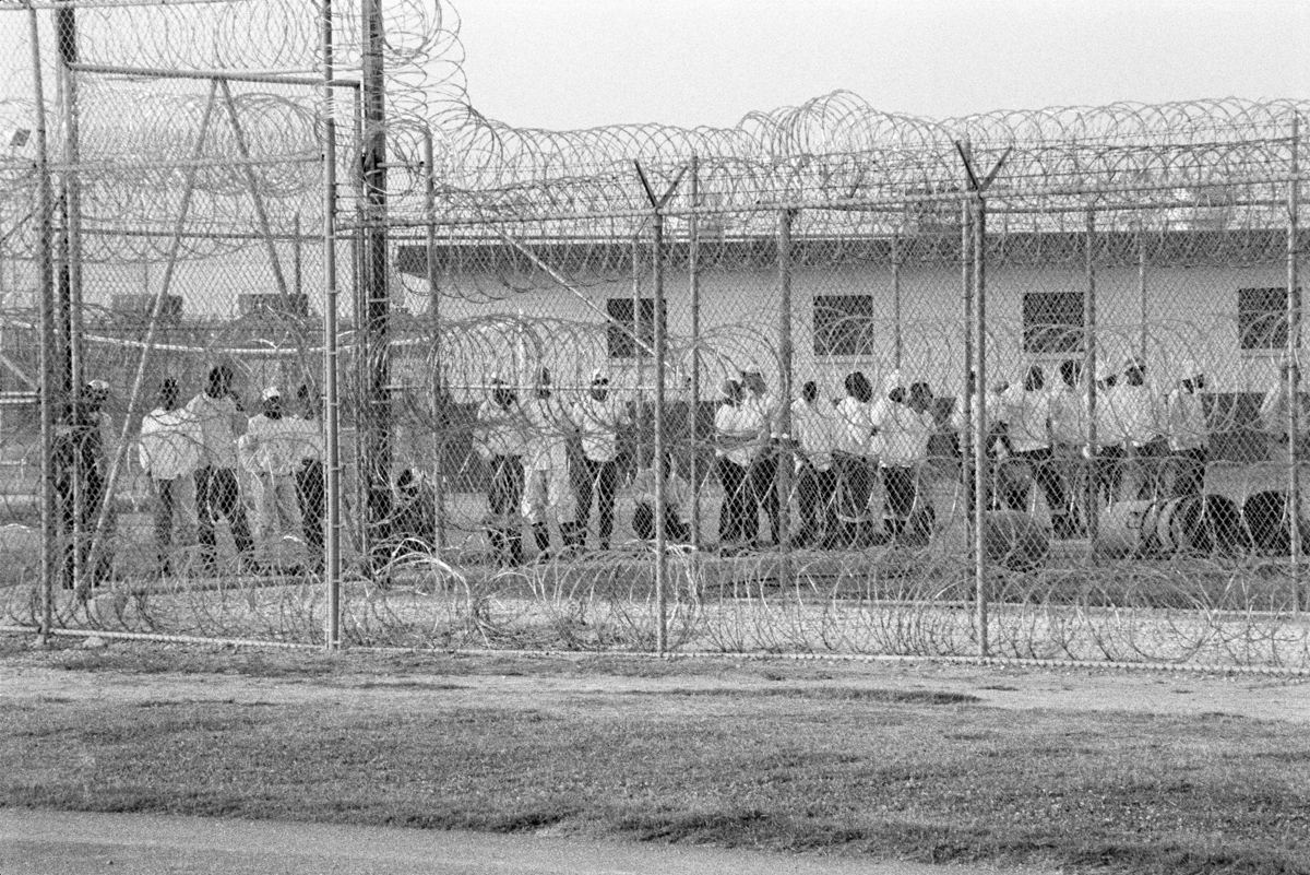 Chandra McCormick, Work Call, Men Behind Barbed Wire Fencing Waiting to Go to Work in the Fields of Angola., 2004. Archival pigment print. Courtesy of the artist.