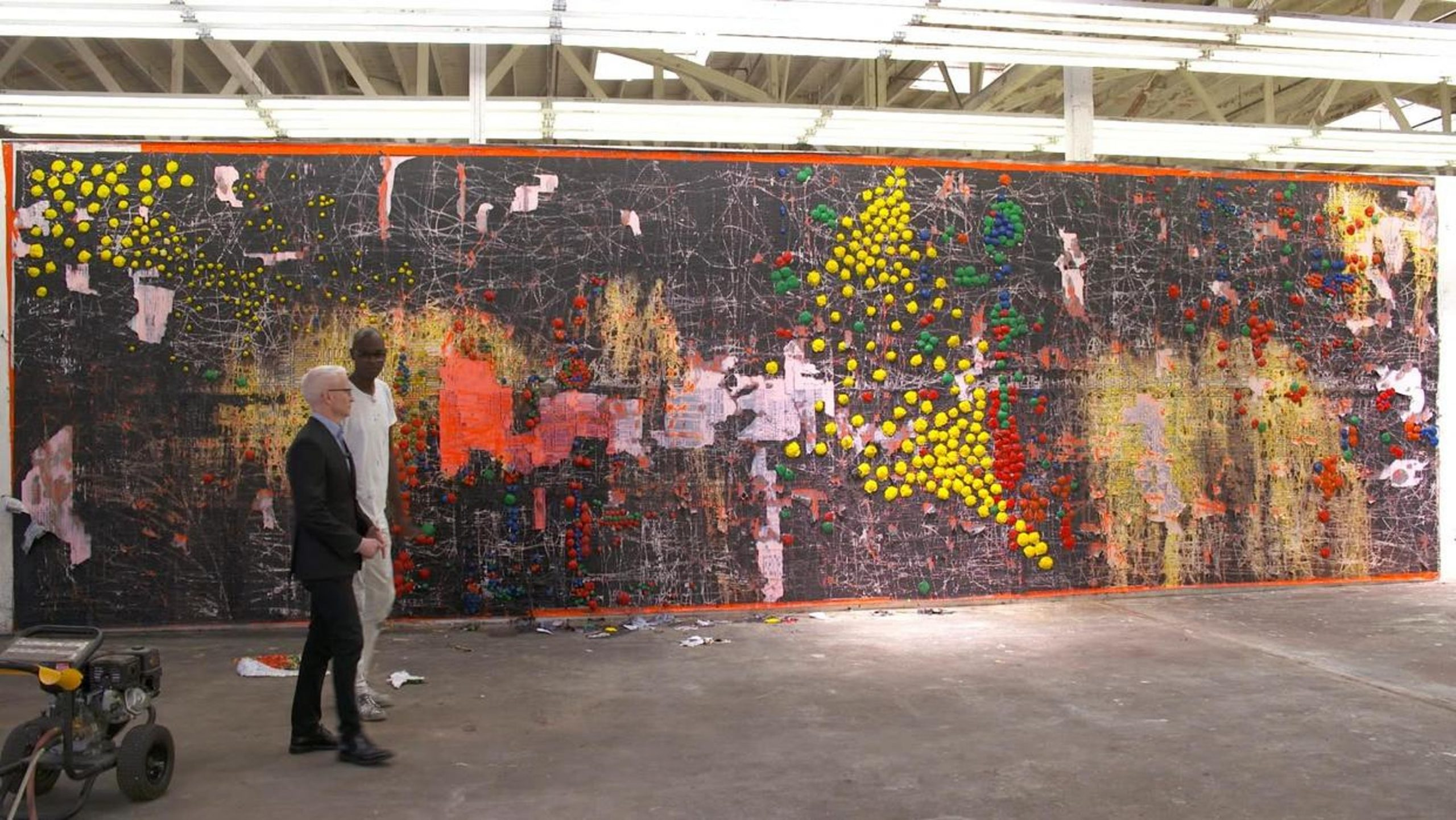 Artist Mark Bradford shows Anderson Cooper one of his pieces.